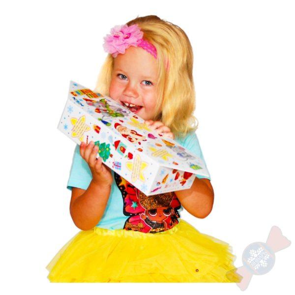 Девочка пробует на вкус подарок Конфета великана